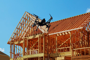 Black drone quadcopter with camera flying over framing of a new house under construction