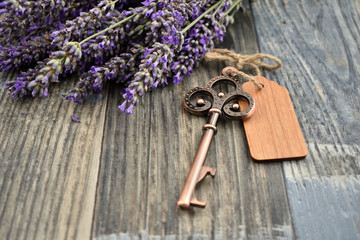 Old key with lavender stock images. Lavender on a wooden background. Decorative metal key images. Romantic key with wooden label. Key on the table