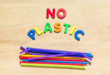 "colorful foam letters spelling the words ""No Plastic"" above a pile of flexible straws on a wooden table"