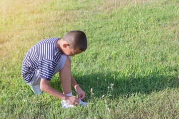 An young Asian boy is lacing white shoe rope. On green grass