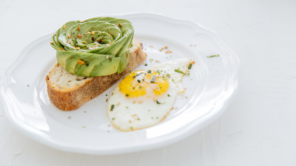 Avocado rose on toast with sunny side up egg on white plate and white background.