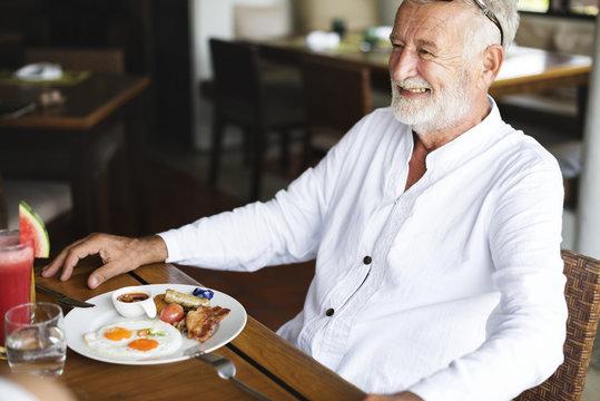 Senior man having breakfast at a hotel