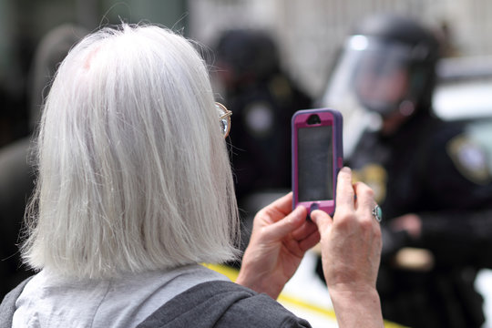 Protestor filming police with her cellphone.