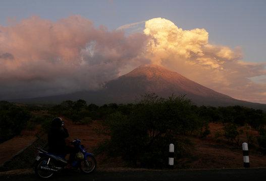 A motorist takes pictures of Mount Agung volcano erupting in Kubu, Karangasem Regency in Bali