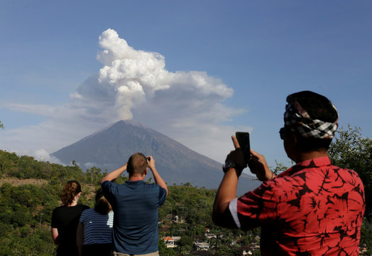 A local guide and foreign tourists take pictures of Mount Agung volcano erupting from Amed, Karangasem Regency in Bali