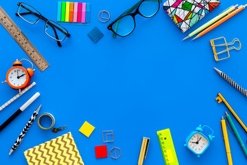 Education background, frame. School, student, office supplies. Stationery, glasses, alarm clock, notebook on blue background top view copy space