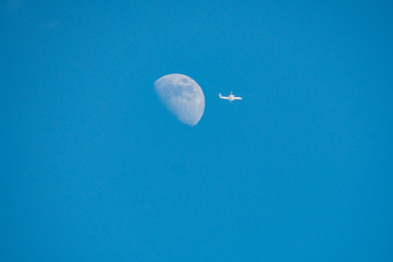 a white plane fly away from the half moon under the blue sky