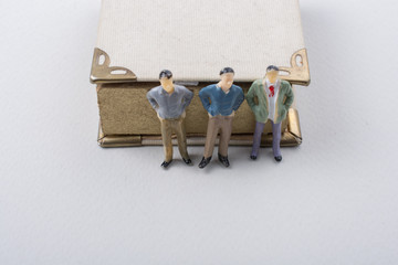 Tiny figurine of men models beside a book