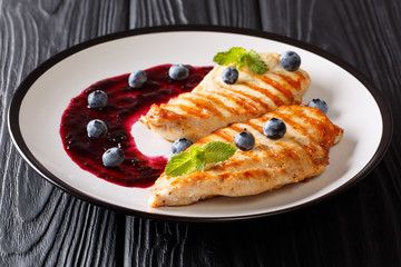 grilled chicken breast served with berry sauce and mint closeup on a plate. Low-calorie. horizontal