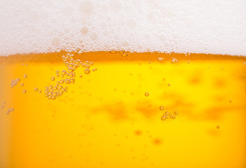 Pouring beer with bubble froth in glass for background. Summer drink texture