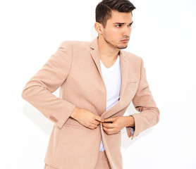 portrait of handsome fashion stylish hipster lumbersexual businessman model dressed in elegant light pink suit posing near white wall in studio. Metrosexual
