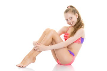 Beautiful little girl in a bathing suit is sitting on the floor.