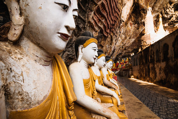 Ancient Buddha statues in a row in Kawgun cave near Hpa-an, Myanmar, Asia