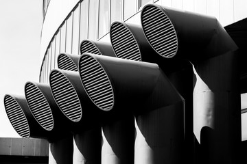 Black and white screensaver, duct pipes with grates on the background of the building.