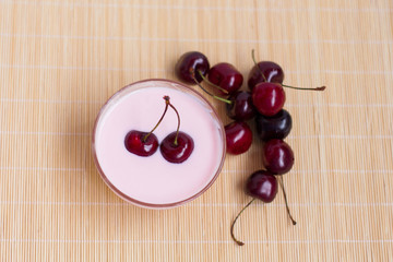Ripe cherries and cherry yogurt are the concept of a healthy diet.