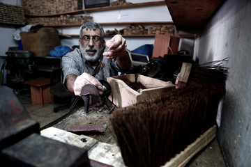 Visually impaired Palestinian man makes cleaning brushes inside a workshop at Blind Caring society, in Nablus in the occupied West Bank
