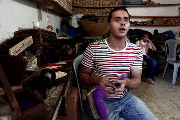 Blind Palestinian man makes cleaning brushes inside a workshop at Blind Caring society, in Nablus in the occupied West Bank