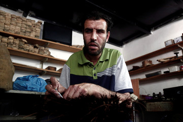 Blind Palestinian man makes a cleaning brush inside a workshop at Blind Caring society, in Nablus in the occupied West Bank