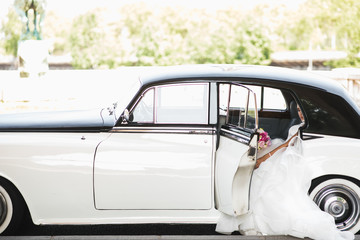 Look from the outside at a bride sitting inside a white retro car
