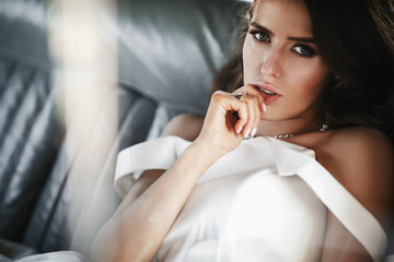 Seductive bride sits inside a white retro car with leather seats
