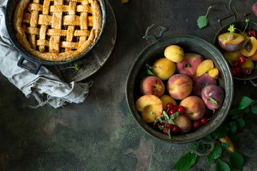 Fruit pie on colorful wooden rustic background with fresh peaches