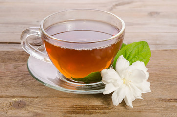 Glass cup of Tea with jasmine flowers on wooden table