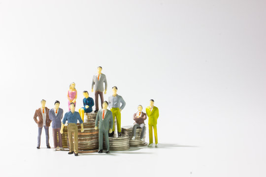 A group of miniature businessman on stack of coins left position.