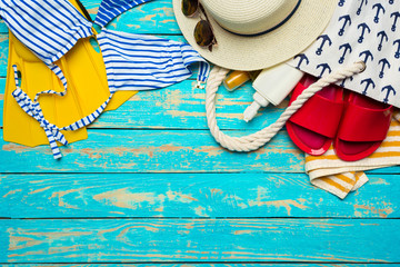 Composition with swimsuit on color wooden background