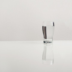 Glass of water on the glass white table with geometrical reflection