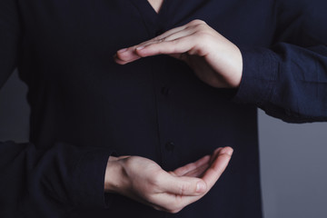 Woman's hands making cupping gesture in front of black shirt