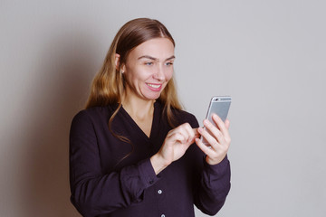 Beautiful blonde smiley woman holding smartphone