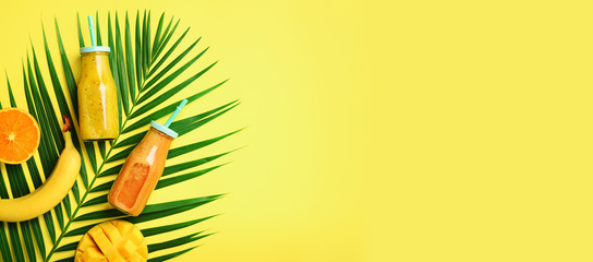 Exotic orange, banana, pineapple, mango smoothie and juicy fruits on palm leaves over yellow background. Banner. Detox summer drink. Organic fruits and vegan concept. Top view, flat lay, copy space