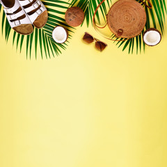 Round rattan bag, coconut, birkenstocks, palm branches, sunglasses on yellow background. Square crop. Top view, copy space. Trendy bamboo bag and shoes. Summer fashion flat lay. Trip, vacation concept