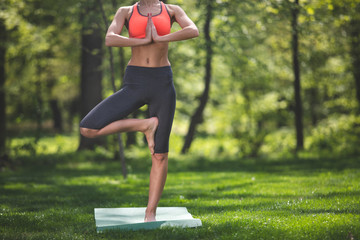 Slim woman is practicing yoga on green lawn. She is standing on one foot and bending another while putting it on opposite thigh. Female is practicing tree pose