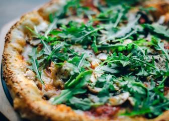 Closeup photo of pizza with fresh basil and rocket salad or arugula