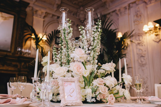 Decorated elegant banquet table in a classic style in the mansion. Decorated with bouquets of white flowers from roses and buttercups, glass candlesticks, cutlery and candles
