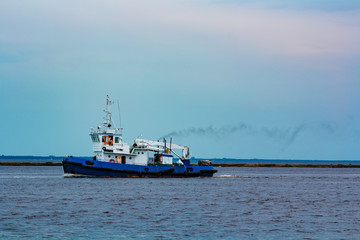 Blue tug ship underway