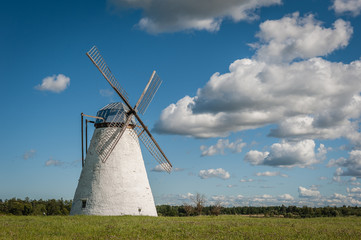 Stone windmill on background field and cloudy sky. Vihula, Estonia.
