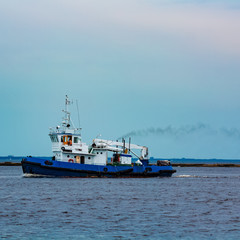 Blue tug ship underway