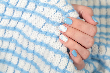 Closeup view of painted blue and white fingernails of young woman isolated on cozy warm blanket. Winter style of manicure. Horizontal color photography.