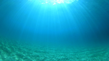 Underwater background with clear blue sea and sandy bottom