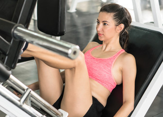 Woman exercise leg muscle on machine in gym.