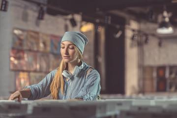 Spoed Foto op Canvas Muziekwinkel Attractive girl in a music store
