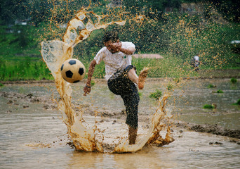 A man kicks a football as he takes part in an event celebrating National Paddy Day, also called Asar Pandra, that marks the commencement of rice crop planting in paddy fields as monsoon season arrives, in Lalitpur