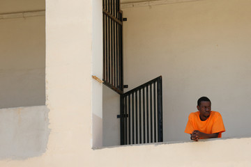 A Migrants waits to be processed and interviewed by authorities at the reception centre for migrants in Marsa