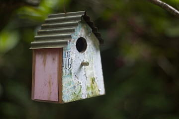 Een fraai vogelhuisje met een golfplaten dakje