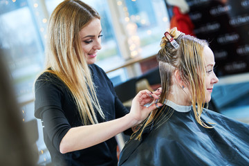Barber or stylist at work. Hairdresser cutting woman hair