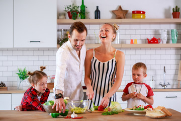 Image of young parents with son and daughter preparing breakfast