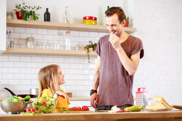 Picture of young father with daughter cooking lunch