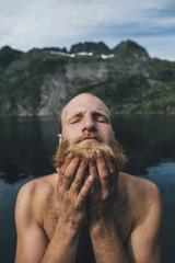 Man washing his beard at lake